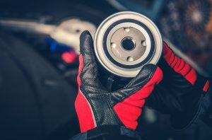 Diesel Engine Oil Filter in Mechanics Hands. Modern Automotive Theme.
